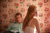 Young couple seated in room with floral wallpaper