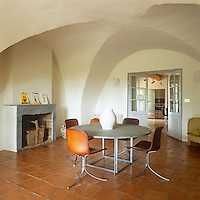A simple, rustic dining room with a vaulted ceiling and terracotta tiled floor. Modern, contemporary furniture contrasts with the original, features of the room and a pair of double doors lead to a kitchen area.