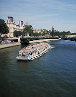 A sightseeing tourist boat travels down the Seine. boats, tourism, waterways, transportation. Paris, France.