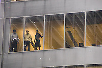 Three office workers in downtown Manhattan view the NY Giants victory parade.