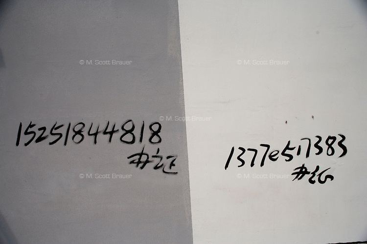 Day laborers' cell phone numbers are scrawled on a wall in Pukou, Jiangsu, China.