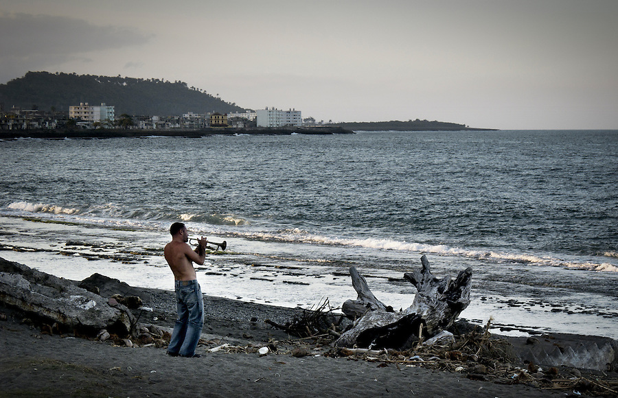 A young cuban playing trumpet by the sea at sunset in Baracoa.
