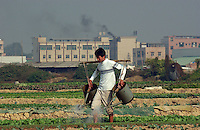 A young farmers waters his fields in front of factories, Changping, China.<br /> 17-DEC-04