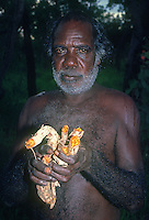 Tribal Aboriginal elder from Arnhem Land in the Northern Territory holding the Roots (from a small special tree) from which the Aboriginals after boiling get the coloring for their natural woven baskets.
