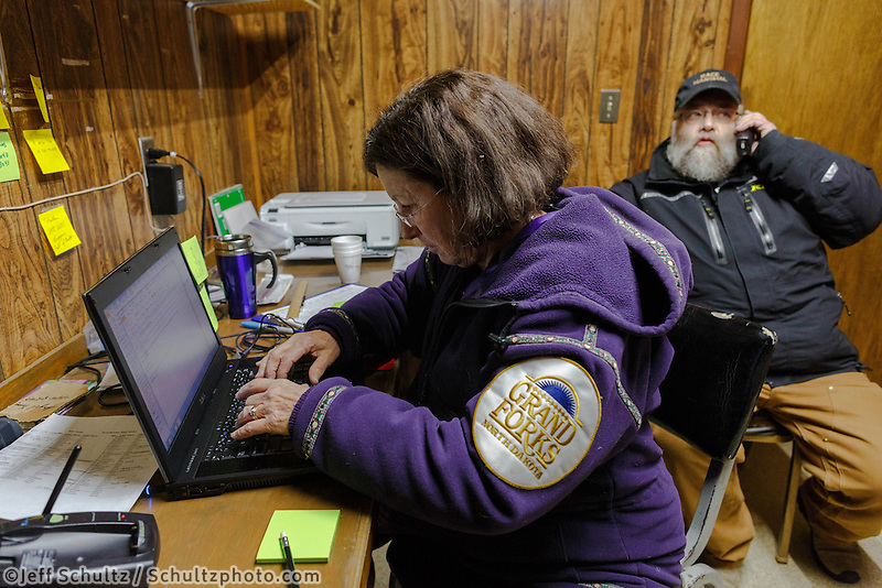 Volunteer comms Nancy Yoshida works on sending musher traffic as race marshal Mark Nordman is on the phone at the Takotna checkpoint, Wednesday, March 5, during the Iditarod Sled Dog Race 2014.<br /> <br /> PHOTO (c) BY JEFF SCHULTZ/IditarodPhotos.com -- REPRODUCTION PROHIBITED WITHOUT PERMISSION
