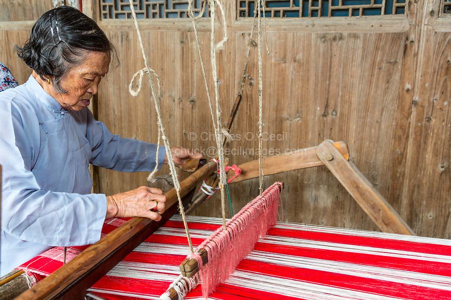 Yubei, Zhejiang, China.  Senior Woman Weaving at her Loom.