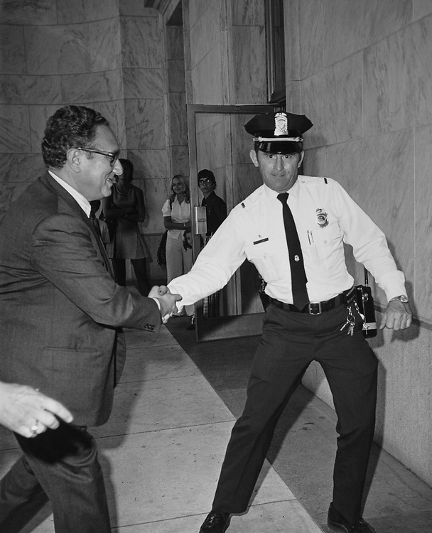 Secretary of State Henry Kissinger being escorted to Rayburn House Office Building by U.S policeman Patril Reece. (Photo by CQ Roll Call via Getty Images)