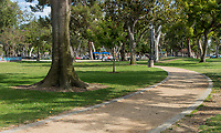 The decomposed granite pathway curves underneath mature trees at South Gate Park, leading to a picnic area full of people in the distance.