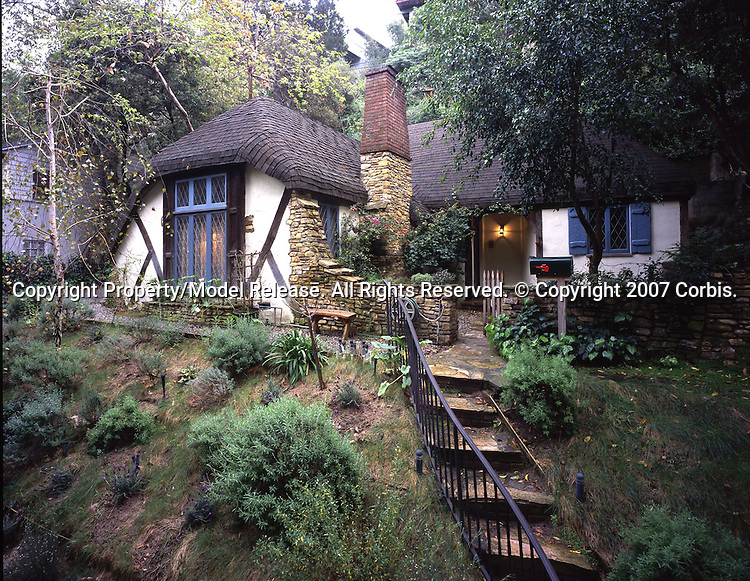 """This cozy abode, reminiscent of an English Cotswold cottage is tucked into a ravine just below the Hollywood sign in Los Angeles. The Hollywood sign originally read """"Hollywoodland"""" and was an advertisement for a housing development begun in 1923. Originally the development was supposed to contain mostly romantic and Storybook style homes, but as budgets and pocketbooks tightened during the Great Depression, regulations were relaxed and more pedestrian homes were built. Still there are many wonderful homes to see in the area and the Storybook style sleuth will be rewarded with glimpses of fanciful homes once owned by stars like Humphrey Bogart, Gloria Swanson and Bela Lugosi. Even Madonna owned one of the larger homes for a while."""