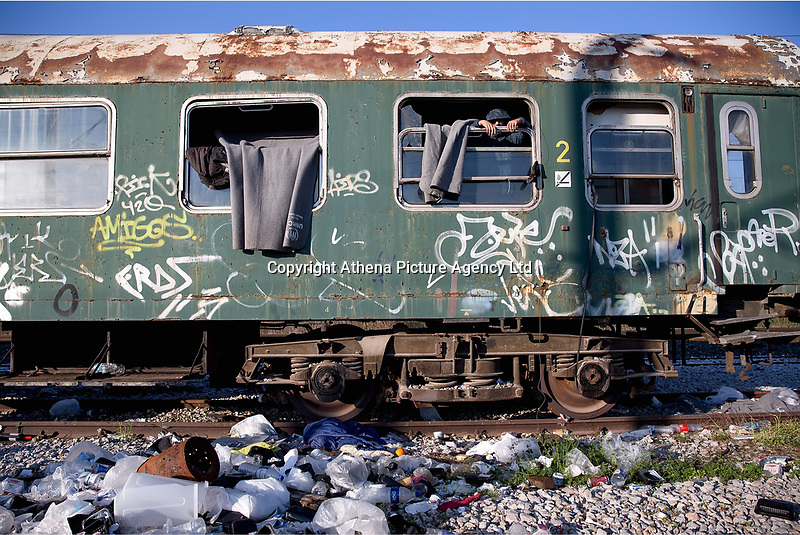 Pictured: A man looks out the window of a disused train carriage he has been living in at the OSE freight depot in Thessaloniki, Greece. Wednesday 05 April 2017<br /> Re: A year after an agreement was signed between Greece and Turkey for the management of refugees. Migrants, mostly from Morocco, Algeria and Tunisia, have been living in disused train carriages at the Thessaloniki freight depot of OSE in northern Greece, the company managing the railways in the country. Some of the migrants climb onto moving trains, or even hide themselves in storage areas, hoping that they will cross the border.
