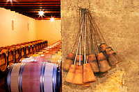 The barrel cellar for aging the wines in oak casks - to the right wooden bung plugs with an iron wire hook that are used for cleaning the barrels with a sulphur pellet - Chateau La Grave Figeac, Saint Emilion, Bordeaux