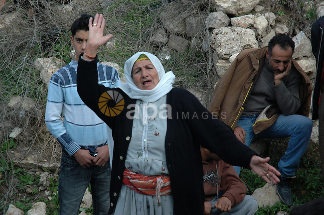 A Palestinian woman reacts after a mosque was vandalized in the West Bank village of Kfar Yasuf, south of the West Bank city of Nablus, on December 11, 2009. Jewish settlers are suspected in the attack on the mosque where fire was set to a library and hate messages were sprayed on the building, Palestinian security sources said. Photo by Nedal Shtieh