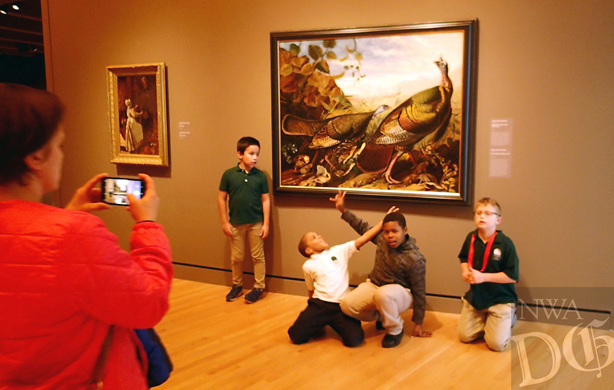 """NWA Democrat-Gazette/FLIP PUTTHOFF <br /> Kids get a souvenir photo taken    Dec. 7 2018 with a painting of wild turkeys by John James Audubon. The title is """"Wild Turkey Cock, Hen and Young"""" and is one of many art works with a nature or wildlife subject at Crystal Bridges Museum of American Art."""