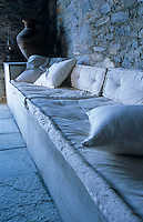 A built-in concrete banquette covered in cushions runs along one wall of the simple open-plan one-room property