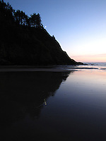The crescent moon hovers near the bluff at sunset, its reflection distorted by ripples in the wet sand.  Haceta Head Lighthouse beach.