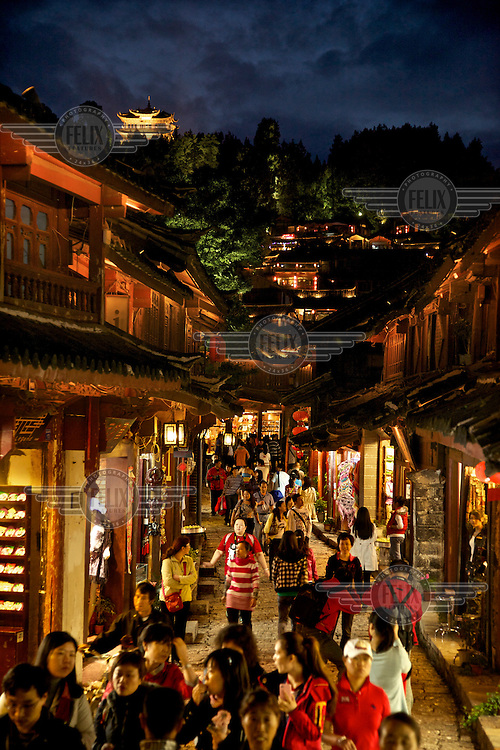 Tourists throng a brightly lit street in Lijiang a town whose historic buildings are a major tourist attraction and an UNESCO World Heritage Site. /Felix Features