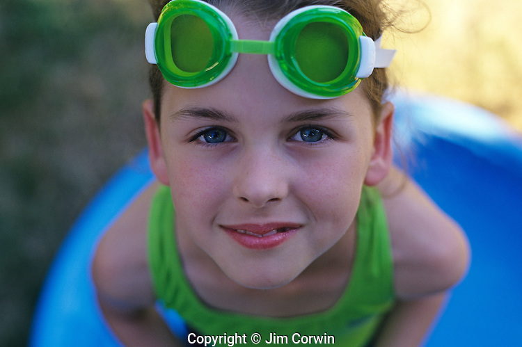 Young girl ( 9 yrs old) with water goggles smiling standing in a wading pool summer fun into camera lens .