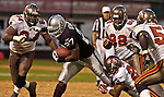 Tampa Bay Buccaneers defensive back Ronde Barber (20) tackles Oakland Raiders running back J.R. Redmond (27) on Sunday, September 26, 2004, in Oakland, California. The Raiders defeated the Buccaneers 30-20.