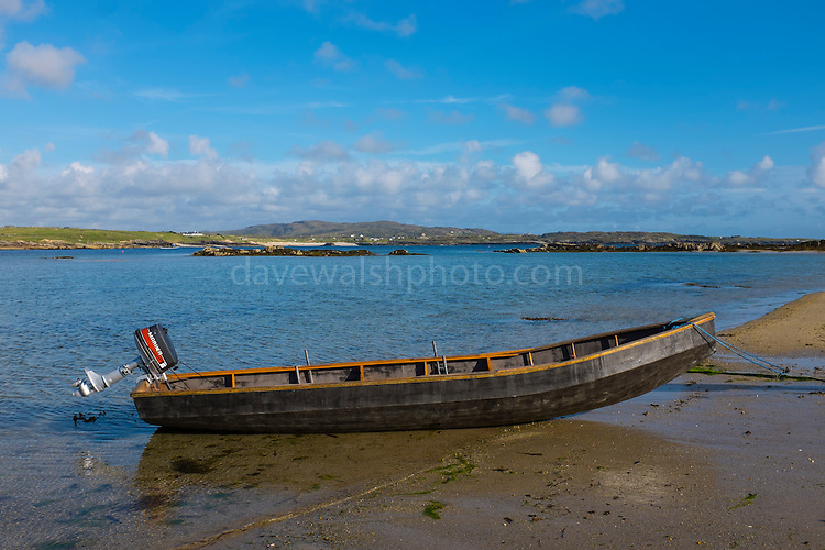 Traditional Curragh, canvas and wood boat on Omey Island at low tide, Connemara, Galway, Ireland. Omey is a tidal island - with a signposted route so that can cars can drive out on the sand during low tide.