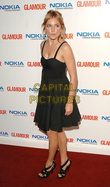 SIENNA MILLER.Attending the 4th Annual Glamour Women Of The Year Awards 2007, Berkley Square Gardens, London, England,.June 5th 2007..full length black dress strappy shoes.CAP/ BEL.©Tom Belcher/Capital Pictures.