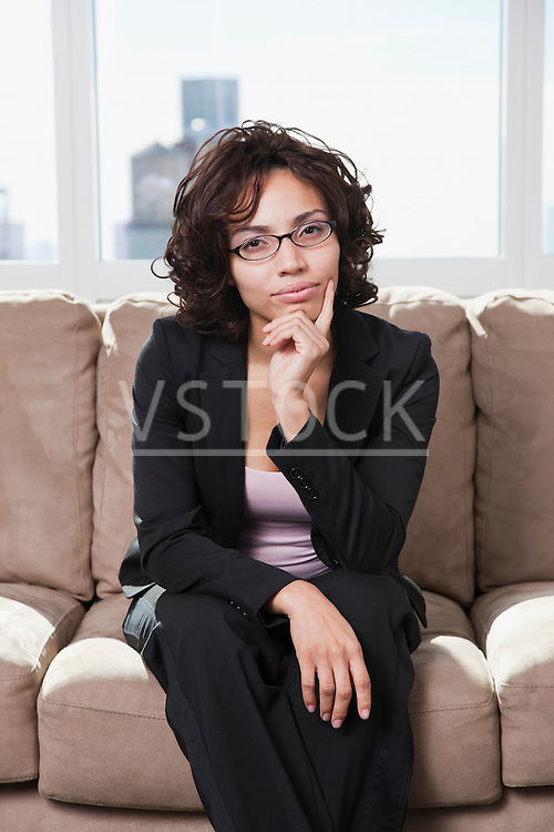 USA, New York State, New York City, portrait of business woman sitting on sofa