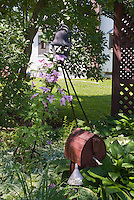 Bird house, climbing pink Clematis vine, ornamental garden bell, shde, house, under the tree, hostas