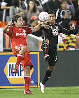 Andy Najar #14 of D.C. United goes for a loose ball with Nick Garcia #4 of Toronto FC during an MLS match that was the final appearance of D.C. United's Jaime Moreno at RFK Stadium, in Washington D.C. on October 23, 2010. Toronto won 3-2.