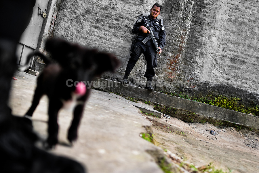 A policeman from the special emergency unit (Halcones) patrols in a gang neighbourhood of San Salvador, El Salvador, 12 December 2013. Although the murder rate in the country has dropped significantly, after a truce between two major street gangs (Mara Salvatrucha and Barrio 18) was agreed in 2012, the lack of security and violence are still the main issues in people's daily life. Due to the fact the gangs have never stopped their criminal activities (extortions, distribution of drugs and kidnappings), the Police anti-gang forces keep running their operations and chasing the 'homeboys' (how the gang's foot soldiers usually call themselves) in the poor, socially deprived suburbs of Salvadoran cities.