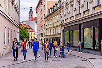 People walking in Ljubljana, with the spire of the Franciscan Church of the Annunciation in the background, Ljubljana, Slovenia, Europe