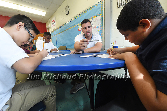 (09/18/17 Springfield MA) Math teacher Evan Christensen works with seventh grade students during a math game on negative and positive numbers, in his classroom at John J. Duggan Academy, Monday, Sept. 18, 2017, in Springfield. The students are from right,  Christopher Marti,  Josue Ruiz, Yasmine Badillo, and Tyshawn Heslope, far left. Herald Photo by Jim Michaud