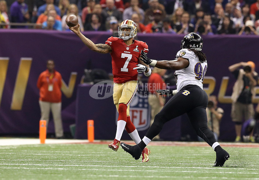 Feb 3, 2013; New Orleans, LA, USA; San Francisco 49ers quarterback Colin Kaepernick (7) throws a pass while pressured by Baltimore Ravens defensive end Pernell McPhee (90) in Super Bowl XLVII at the Mercedes-Benz Superdome. Mandatory Credit: Mark J. Rebilas-
