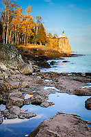 Split Rock Lighthouse on the north shore of Lake Superior with colorful autumn trees.