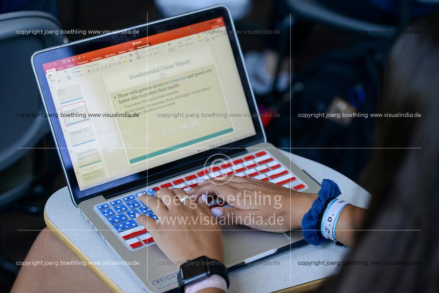 USA, Nebraska, Omaha, Creighton University, student with apple notebook with keyboard with american flag