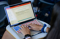 USA, Nebraska, Omaha, Creighton University, student with apple notebook with keyboard with american flag