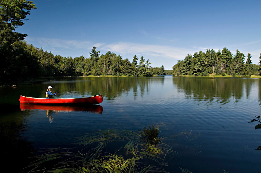 A female canoeist paddles solo on Big Bateau Lake at Sylvania Wilderness Area of Ottawa National Forest near Watersmeet Michigan.