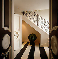 View through open double doors to the entrance hall which is decorated with a striking black and white striped floor
