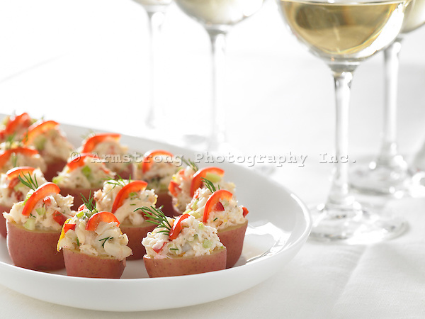 Appetizer tray with glasses of white wine. Small red potatoes with dungeness crab, red pepper, dill