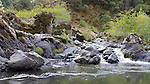 A side creek pours over bedrock into the Rogue River.
