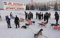 Sunday February 26, 2006 Willow, Alaska.  Rohn Buser crosses the finish line to place second in the 2006 Junior Iditarod.  The team resting in the foreground is first place finisher Michael Degerland.