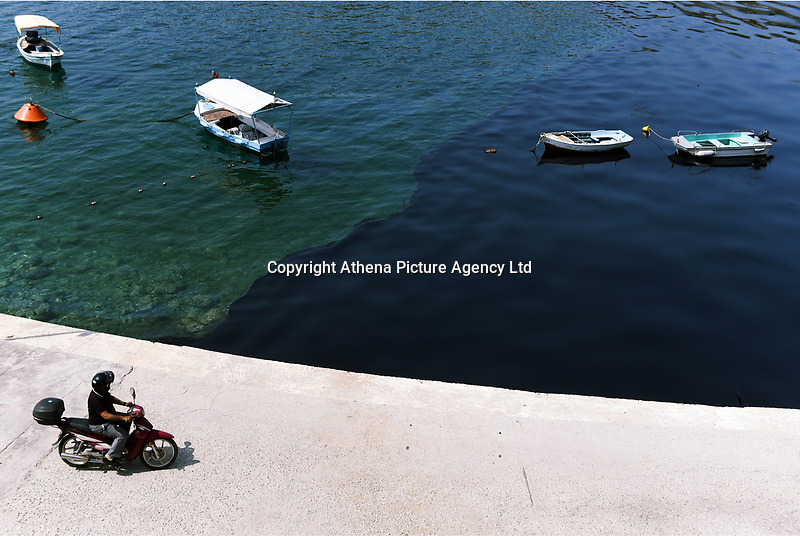 "Pictured: The oil spill moving slowly towards the coast of Salamina, Greece<br /> Re: An oil spill off Salamina island's eastern coast is spreading and has become ""an environmental disaster"" according to local authorities in Greece.<br /> The spill was caused by the sinking of the Aghia Zoni II tanker, carrying 2,200 metric tons of fuel oil and 370 metric tons of marine gas oil on Saturday, southwest of the islet of Atalanti near Psytalleia. According to reports, the coastline stretching from Kinosoura to the Selinia community has ""turned black"" and authorities fear a new leak from the sunken ship.<br /> According to the island's mayor, Isidora Papathanasiou, the weather ""turned on Sunday afternoon and brought the oil spill to Salamina."""
