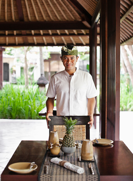 Young Balinese waiter sets table for lunch at The Gong restaurant, Kayumanis Gangsa, Bali, Indonesia.