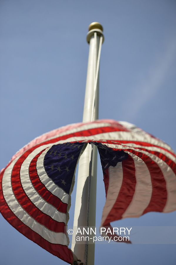 Merrick, New York, U.S. - May 26, 2014 - The American flag is lowered to half-mast during the Merrick Memorial Day Parade and Ceremony, hosted by American Legion Post 1282 of Merrick, honoring those who died in war while serving in the United States military.