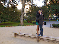 USA. New York City. Union Square Park. A couple of asian lovers hold each other in their arms while stannding up on a wood bench. The woman wears a green tight mini skirt and high-heels shoes, the man casual clothes. 25.10.2011 © 2011 Didier Ruef