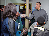 United States President Barack Obama hands out sweet potatos to the needy at Bread for the City in Southeast Washington, Wednesday, Nov. 26, 2014. The president and first family were participating in their annual tradition of distributing food at Thanksgiving.<br /> Credit: Martin H. Simon / Pool via CNP