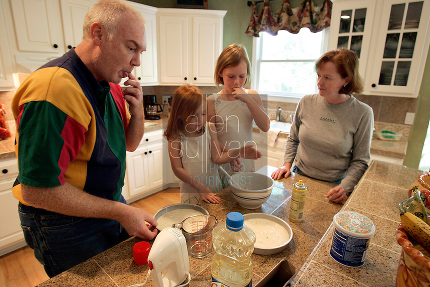 David Wood (from left), Abigayle, 5, Caroline, 8, and Anna Marie Wood make Abigayle's birthday cake at home in Lawrenceville, Ga. on Sunday, Sept. 10, 2006. Abigayle was born on Sept. 11, 2001. Anna Marie Wood said the attacks on that day caused her to go into early labor.<br />