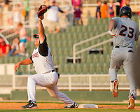 Dan Black #40 of the Kannapolis Intimidators snags a high throw as Kipp Schutz #23 of the Delmarva Shorebirds hustles down the first base line at Fieldcrest Cannon Stadium on May 22, 2011 in Kannapolis, North Carolina.   Photo by Brian Westerholt / Four Seam Images