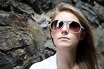 A pretty blond teenage girl wears sunglasses next to a stone wall.