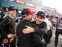 Sep 27, 2019; Madison, IL, USA; NHRA top fuel driver Steve Torrence is hugged by Jonnie Lindberg as Austin Prock looks on during qualifying for the Midwest Nationals at World Wide Technology Raceway. Mandatory Credit: Mark J. Rebilas-USA TODAY Sports