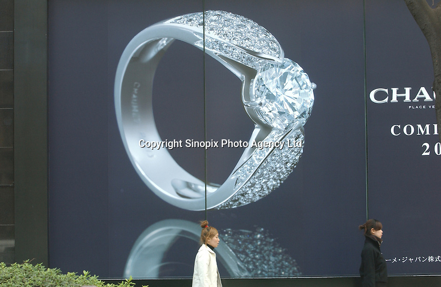 People pass an advert for a Diamond ring and jewellery in Harajuku district in Tokyo, Japan. .Mar 2002
