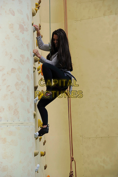 Katie Price (Jordan) .Walkers Crisp Deep Ridged Launch Climbing Wall at Truman Brewery, London, England..August 29th, 2012.full length grey gray top black leggings harness rope side sport exercise looking down leg up.CAP/CAS.©Bob Cass/Capital Pictures.